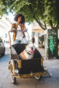 Smiling woman riding bicycle cart with bulldog on cobbled street - MASF10928