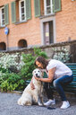 Full length of senior woman embracing dog while sitting on bench at park - MASF10934
