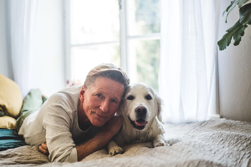 Close-up portrait of senior man and dog lying on bed at home - MASF10943