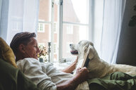 Senior man reading book while relaxing with dog on bed at home - MASF10946