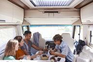 High angle view of family looking at laptop while sitting in camper van - MASF10955