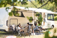 Family relaxing on chairs outside camper van at campsite during summer vacation - MASF10958