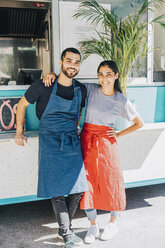 Full length portrait of smiling young colleagues standing against food truck - MASF10988