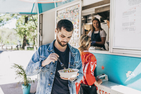 Young man eating fresh Tex-Mex in bowl against food truck - MASF10997