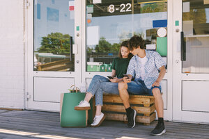 Siblings using mobile phone while sitting on bench with bags outside information booth - MASF11036