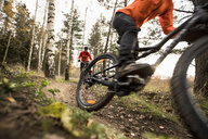 Female friends riding mountain bikes in forest - MASF11045