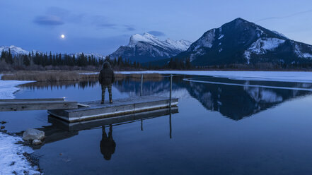 Woman on tranquil winter lake dock, looking at full moon above mountains, Banff, Alberta, Canada - FSIF03717
