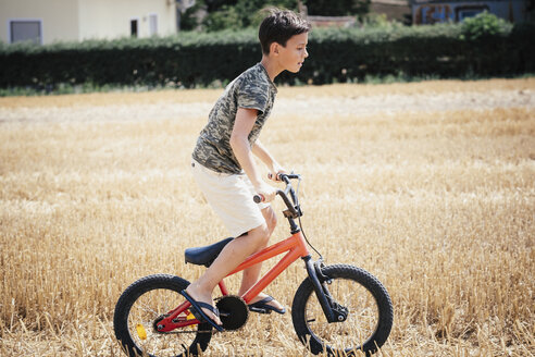 Boy riding bicycle in sunny rural field - FSIF03732