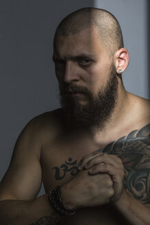 Portrait tough man with beard and tattooed chest, making fist - FSIF03765