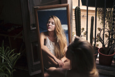 Young woman with long blonde hair looking herself in the mirror at her bohemian home. Spain, Catalonia, Barcelona. - LOTF00051