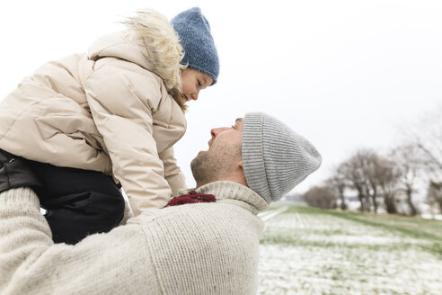 Wickede, NRW, Deutschland. Ein Vater spielt  mit seiner Tochter im Freien beim ersten Schnee - KMKF00679