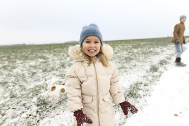 Portrait of happy girl with dog and brother in winter landscape - KMKF00682