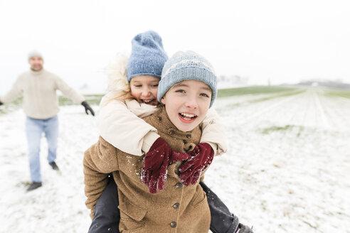 Boy carrying happy sister piggyback in winter landscape - KMKF00685