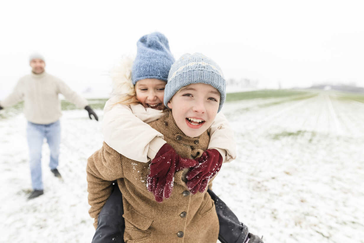 Boy carrying happy sister piggyback in winter landscape - KMKF00685 - Katharina Mikhrin/Westend61