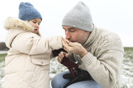 Father warming cold hands of daughter in winter - KMKF00688