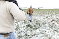 Father, son and dog running on snowy field in winter - KMKF00691