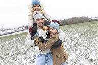 Happy father with two children and dog in winter landscape - KMKF00694