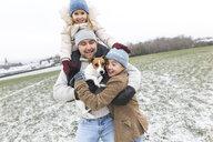 Wickede, NRW, Deutschland. Ein Vater spielt  mit den Kindern und einem Jack Russell Terrier Hund  mit Schnee im Winter im Freien - KMKF00694