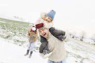 Playful father carrying daughter piggyback in winter landscape - KMKF00697