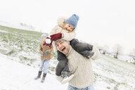 Wickede, NRW, Deutschland. Ein Vater spielt  mit den Kindern mit Schnee im Winter im Freien - KMKF00697