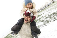 Playful father carrying daughter piggyback in winter landscape - KMKF00700