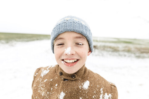 Happy boy playing with snow in winter - KMKF00706