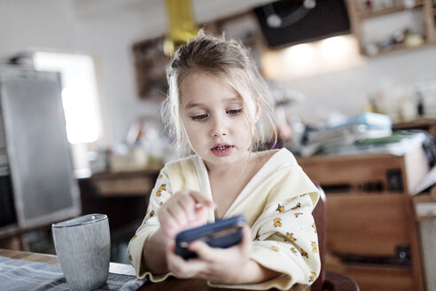 Portrait of little girl sitting at breakfast table in the kitchen using smartphone - KMKF00715