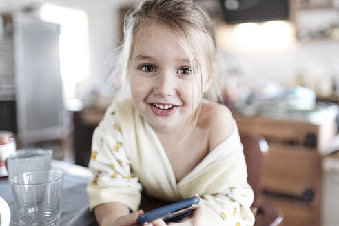 Portrait of smiling little girl with smartphone in the kitchen - KMKF00718