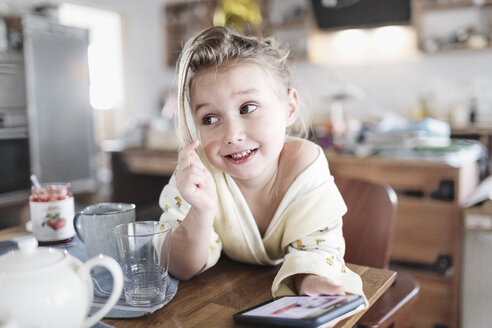 Wickede, NRW, Deutschland. Ein kleines lachendes Mädchen sitzt in der Küche mit einem Smartphone - KMKF00721