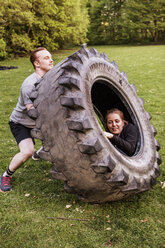Man lifting woman sitting in tire at grassy field - ASTF02240