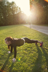 Young woman doing push-ups on grassy field in park - ASTF02246