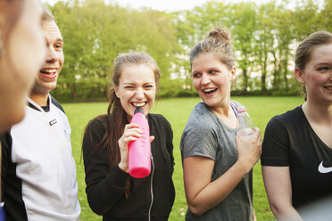 Happy friends drinking water at grassy field - ASTF02267