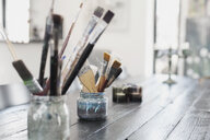 Paint brushes in containers on table - ASTF02294