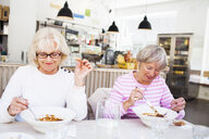 Senior women eating food on table at restaurant - ASTF02381