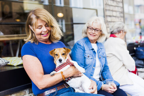 Senior woman holding dog at cafe - ASTF02396