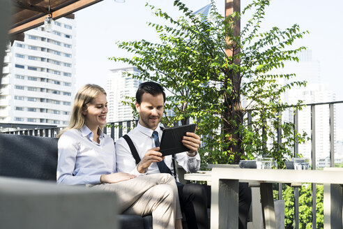 Smiling business colleagues on city terrace looking at tablet - SBOF01549
