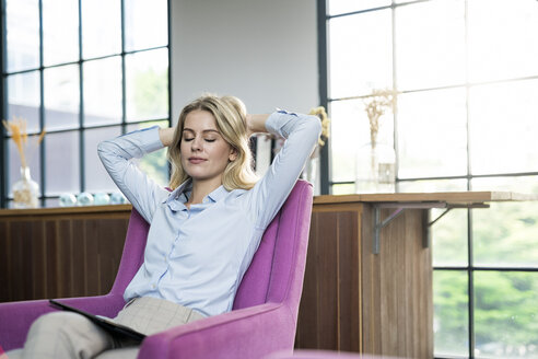 Relaxed blond businesswoman sitting on violet armchair with tablet - SBOF01552