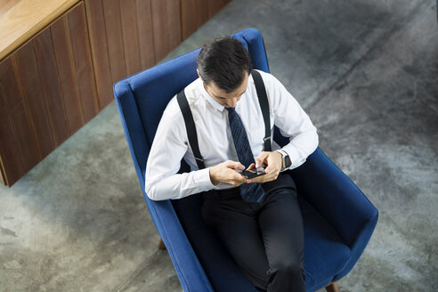 birds view of dark-haired business man working on smartphone on blue armchair in coworking space - SBOF01558