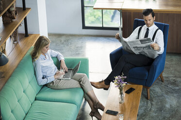 Business colleagues with laptop and newspaper in coworking space - SBOF01561