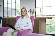 Content blond businesswoman sitting on violet armchair with tablet - SBOF01564