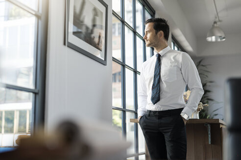 Confident businessman standing in office looking out of window - SBOF01567