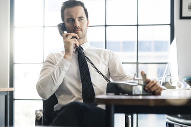 pensative business man in office using vintage retro telephone - SBOF01570