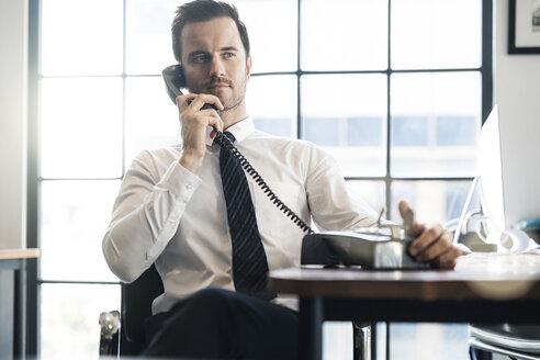Businessman in office using vintage retro telephone - SBOF01570