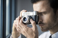 Close-up of businessman taking picture with vintage retro camera in front of office window - SBOF01576