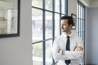Confident businessman standing in office looking out of window - SBOF01579