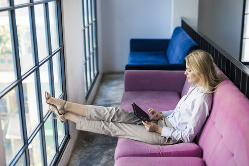 Blond businesswoman sitting on violet couch at the window using tablet - SBOF01582