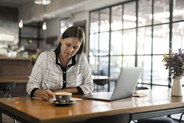 Young businesswoman in a cafe writing on paper and working with laptop on wooden table - SBOF01585