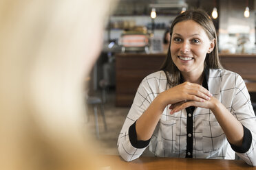 Smiling young businesswoman in cafe talking to colleague - SBOF01594