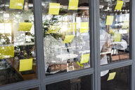 Businessman with colleague brainstorming with post-its on window front - SBOF01597