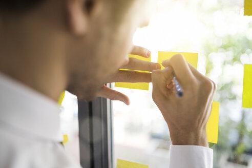 Businessman writing on yellow post-its on window - SBOF01600